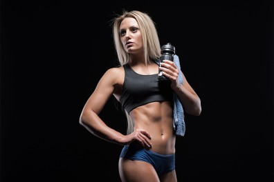 female-posing-with-water-bottle-and-towel-over-black-background